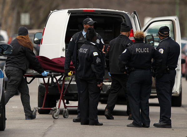 The body of a shooting victim is removed from the scene in the 7400 block of South Eberhart Avenue.