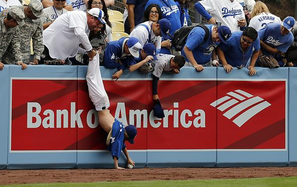 Exhuberant fans go after a foul ball as the Dodgers take batting practice before the season opener against the San Francisco Giants on Monday at Dodger Stadium.