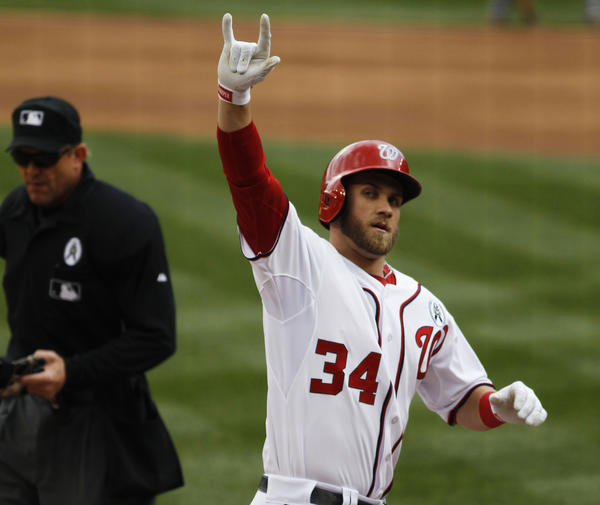 Bryce Harper waves to the crowd after he hits a home run in his first at-bat on opening day.