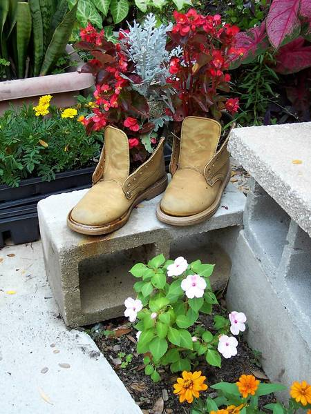 A pair of outgrown boots finds new life as a container for impatiens and dusty miller plants.