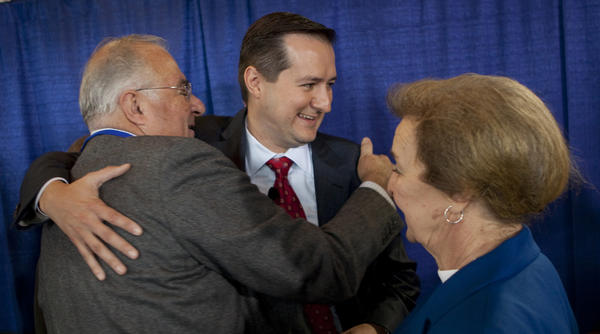 Tom Ricketts (center) gets a hug from his parents Joe and Marlene Ricketts in 2009.