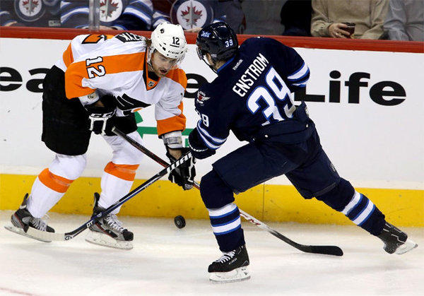 Harry Zolnierczyk (12) and Winnipeg Jets' Tobias Enstrom (39) battle for control of the puck.