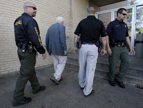 Kaufman County, Texas, law enforcement officials escort an employee inside the county courthouse. Security was increased after a second prosecutor was shot and killed.