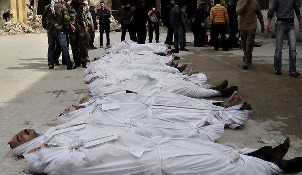 A photo taken by a citizen journalist on March 10, which was provided by Aleppo Media Center and authenticated based on its contents and other Associated Press reporting, shows Syrians standing next to bodies that have been pulled from the river in Aleppo. More than 6,000 people were killed in the Syrian civil war in March alone, according to a leading activist group.