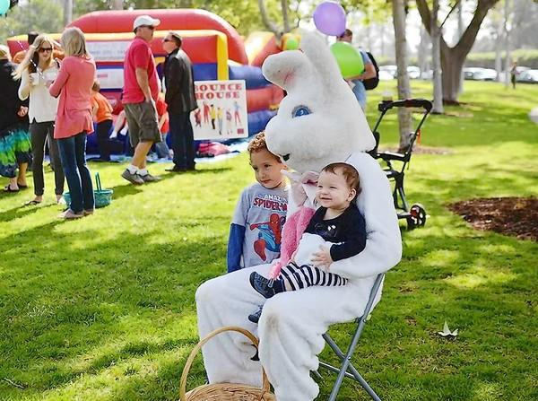 Mateo Balderrama, 3, left, and Lukas Balderrama, 7 months, pose for a picture with the Easter Bunny at Tanager Park in Costa Mesa on Saturday.