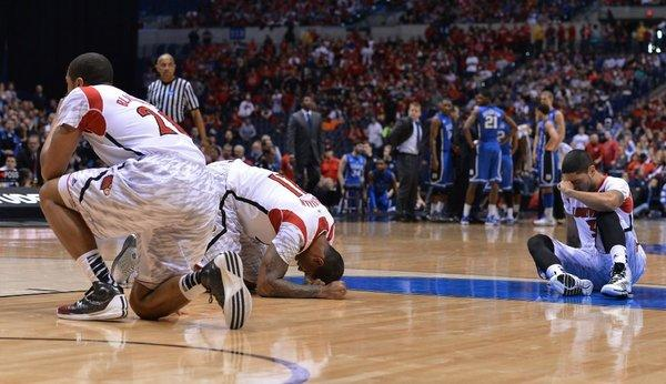 Louisville players collapse on the floor after teammate guard Kevin Ware broke his leg in the first half of an NCAA Tournament game at Lucas Oil Stadium in Indianapolis.
