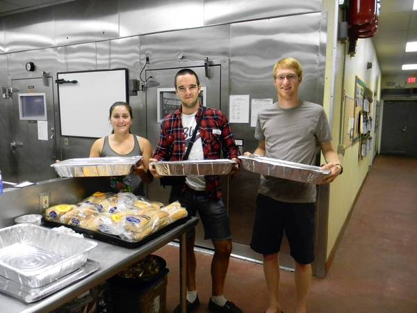 Pomona College students Alana Springer, left, Nick Murphy and Andrew Yost collect leftover food from a campus dining hall. The leftovers are driven to a nearby nonprofit shelter for people in need.