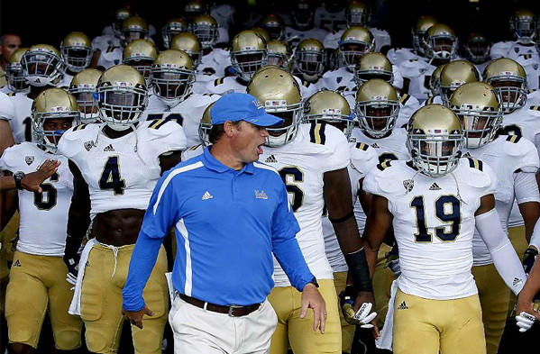 Coach Jim Mora leads the UCLA Bruins to the field to take on the Rice Owls last August.