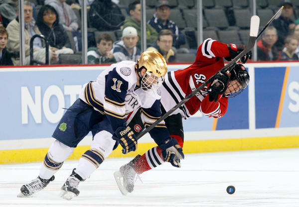 Notre Dame's Jeff Costello (11) collides with St. Cloud State's Ethan Prow (12) during Saturday's regional semifinal hockey game at Huntington Center in Toledo, Ohio. (AP Photo/The Blade, Andy Morrison)