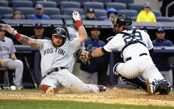 Boston's Jonny Gomes (left) slides safely into home plate past Yankees catcher Francisco Cervelli in the ninth inning.