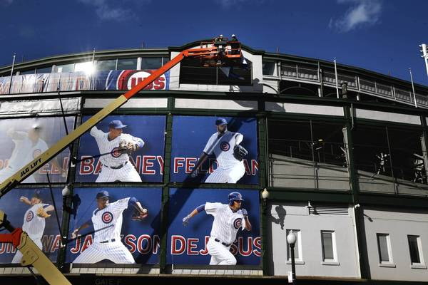 Workers put up banners at Wrigley Field on Monday in Chicago.