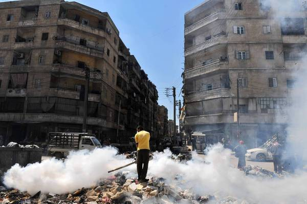 A man fumigates a street covered with uncollected garbage in Aleppo, northern Syria. Parts of the city are under opposition control while others remain in government hands.