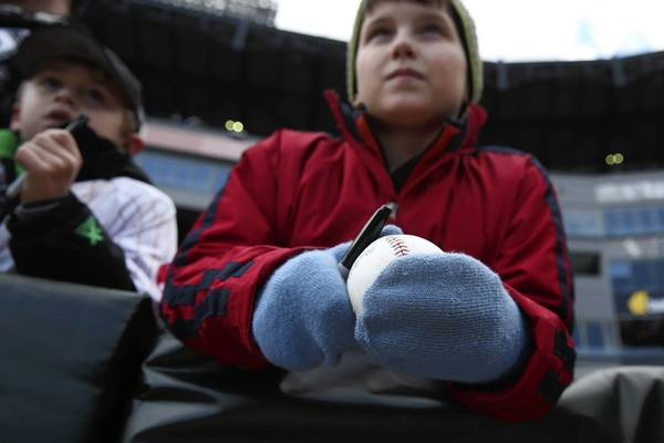 White Sox fan Billy Kacey, 11, of Hinsdale, wears mittens as he waits to get autographs before the team plays the Kansas City Royals on opening day at U.S. Cellular Field.