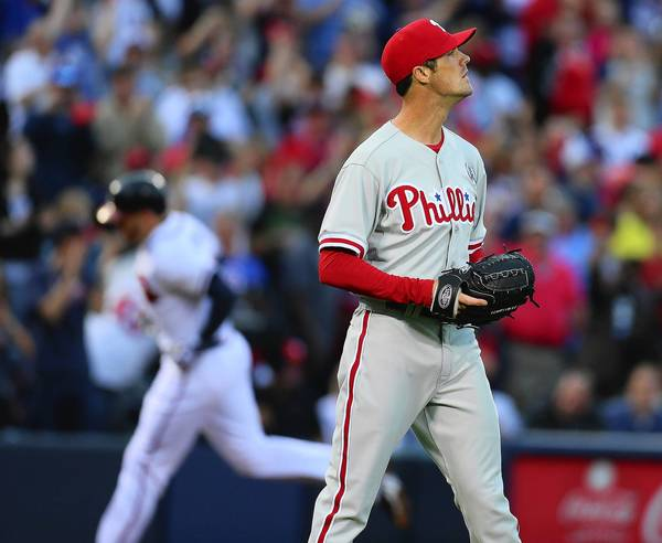 Phillies starter Cole Hamels walks behind the mound as Atlanta's Freddie Freeman rounds third base after belting a 2-run homer in the first inning.