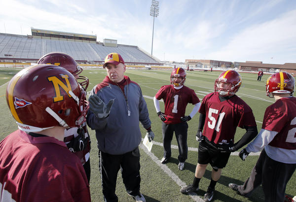 Northern State football coach Tom Dosch, center, talks to a group of defensive players during a recent spring practice at Swisher Field. American News Photo by John Davis