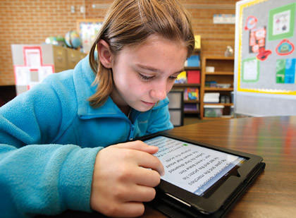 Julia Kolasch, a fifth-grader at May Overby Elementary School, uses an iPad to read from one of her textbooks.