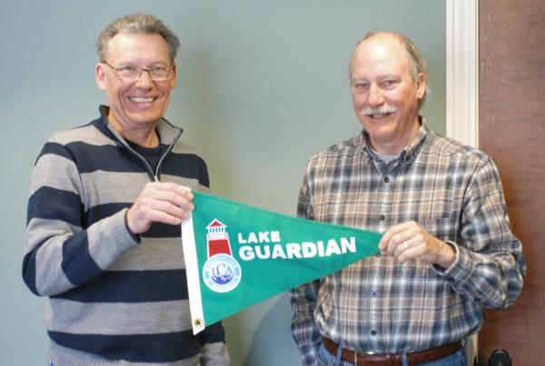 Dan Mishler (left) and Joe Kimmell hold up a burgee they hope to see flying on docks along the shore of Lake Charlevoix this summer. The two are members of the Lake Charlevoix Association, which is launching its lake guardian program for the first time this year.