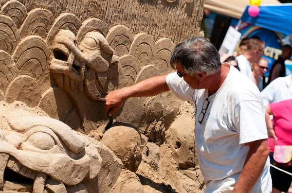 Sand sculptor Ted Siebert works on last year's attraction at RiverFest. This year's sand sculpture will be moved to a new location because of construction at the Municipal Building.