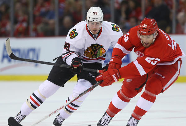 Jimmy Hayes (left) of the Chicago Blackhawks forechecks Brian Lashoff of the Detroit Red Wings on Sunday.