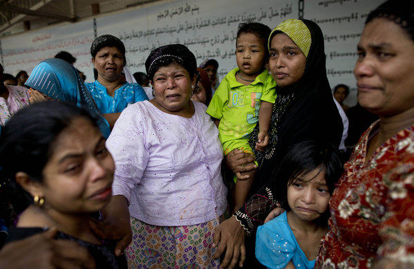 Women cry during burials of the victims of a mosque fire on the outskirts of Yangon, Myanmar.