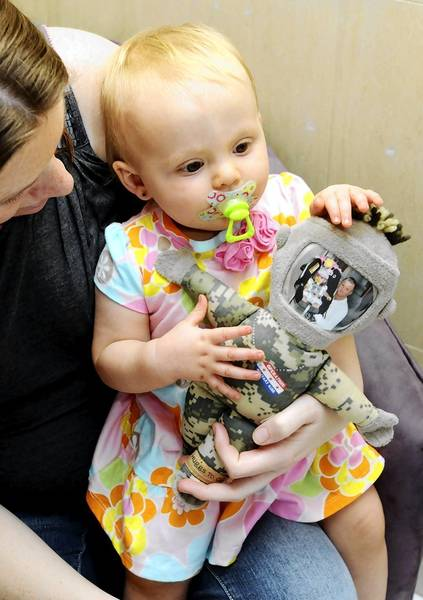 "13-month-old Harley Ann Lubic keeps her deployed father near with her ""daddy doll."""