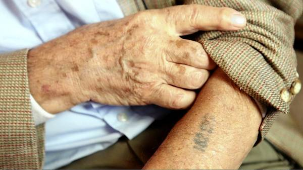 "In a scene from ""Bearing Witness: The Voices of Our Survivors,"" a documentary film currently featured at the Palm Beach Film Festival, a Holocaust survivor displays his concentration camp tattoo."