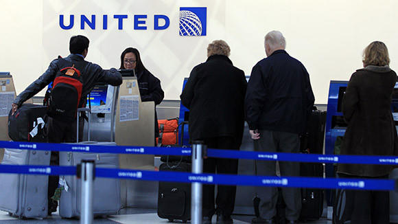 United Airlines workers help passengers at the counter in Terminal 1 at Chicago O'Hare International Airport on Thursday, November 15, 2012.