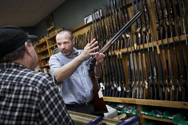 Redding Vice Mayor and the owner of a gun shop Patrick Jones, right, shows a customer, John Robinson of Redding, a shotgun in his store this year. State lawmakers are considering new gun control measures.