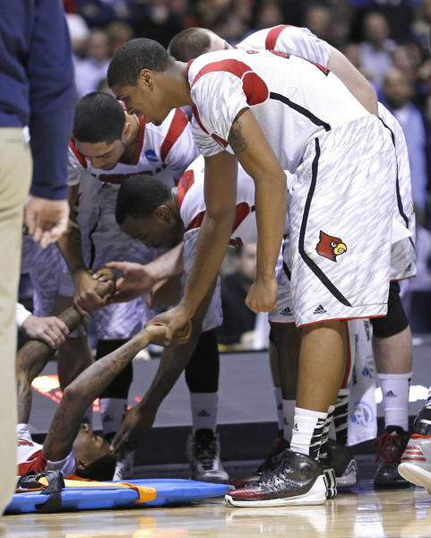 Kevin Ware is comforted by his teammates after his injury Sunday.