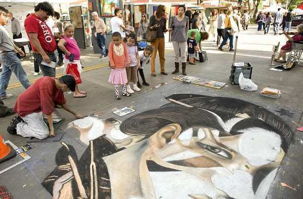 Gustavo Lozano works on a piece of sidewalk art during a Downtown Burbank Fine Arts Festival on San Fernando Blvd.