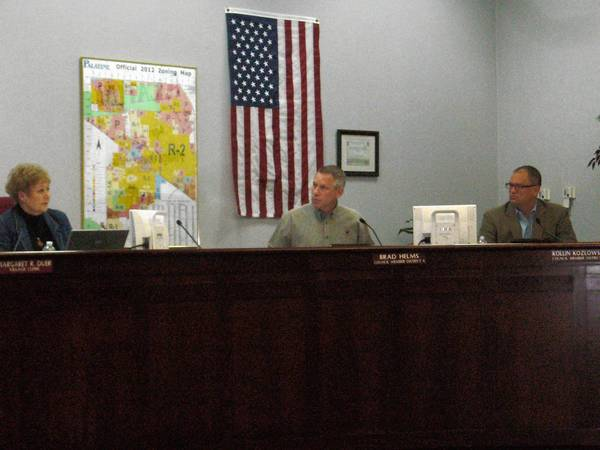 Village Clerk Margaret Duer and Council members Brad Helms and Kollin Kozlowski discuss issues at the council's April 1 meeting.