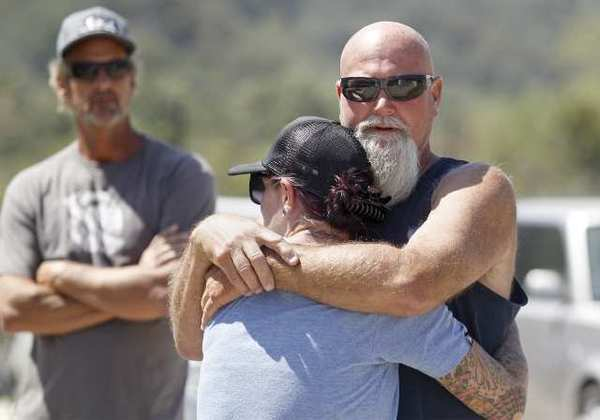 Russ Jack, Kyndall's father, far right, shares a hug as he waits for news about the two missing hikers in Trabuco Canyon on Tuesday.