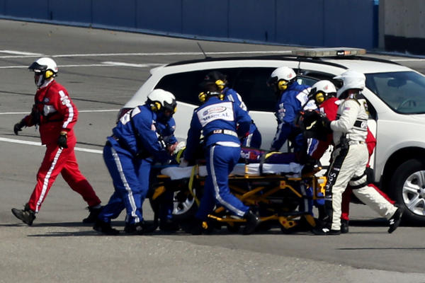 Safety workers attend to Denny Hamlin after an incident with Joey Logano on the final lap during the NASCAR Sprint Cup Series Auto Club 400 at Auto Club Speedway.