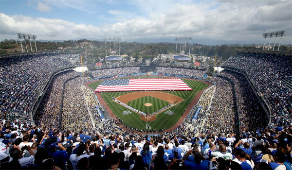 The crowd and participants stand for the national anthem as a giant American flag is unfurled on the field on opening day at Dodger Stadium.