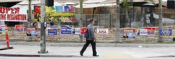 Several election signs in a small strip of grass between the sidewalk and a restaurant patio on the corner of Central Avenue and Lexington Drive in Glendale.