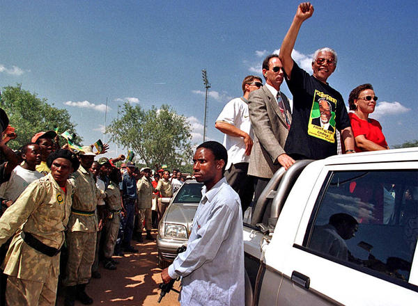 Mandela rides in the back of a truck during a preelection rally near the end of his tenure as president.