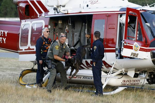 Bill Burk of the Orange County Sheriff's Department, with his dog Sando, gets out of a helicopter at Holy Jim Canyon to search for the lost hikers.