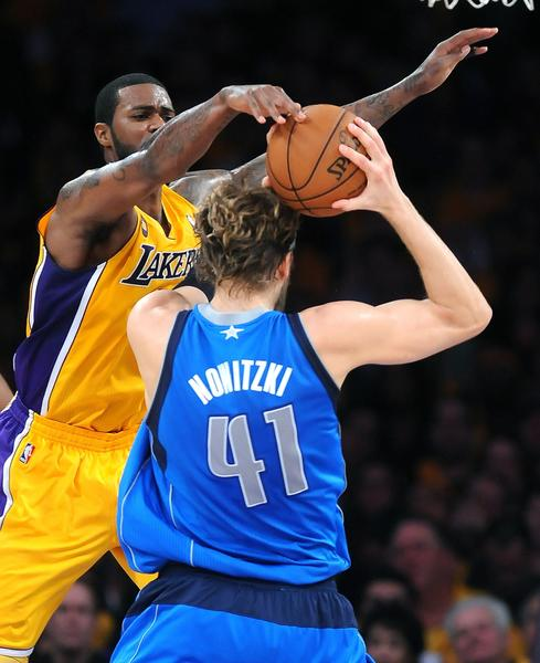 Lakers forward Earl Clark alters the shot of Dallas Mavericks forward Dirk Nowitzki.
