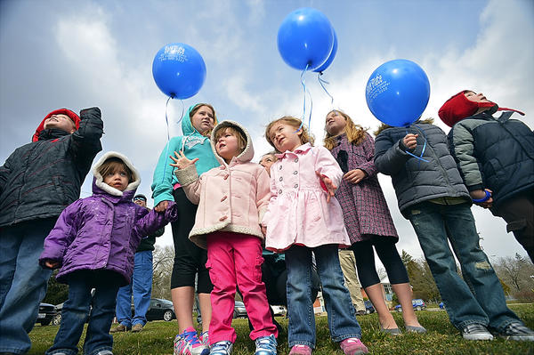Hailey Mackey, center, and her friend Abigail Close release balloons Tuesday at the start of a child abuse awareness event in Hancock's Widmeyer Park. From left are Mason Starliper, Zuleika Valladares, Josie Foltz, Hailey Mackey, Abigail Close, Alexandra Smith, Nicole Starliper, and Benjamin Barnhart. Alexandra was a helper Tuesday with the students from Good Shepherd Preschool.