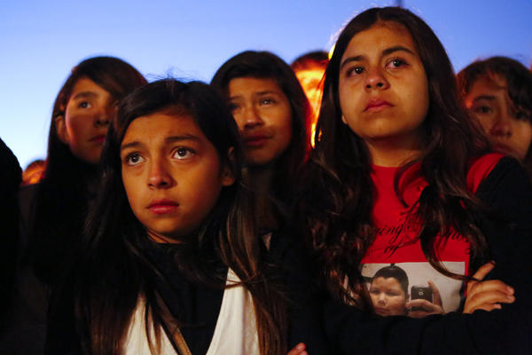 A young girl wears a T-shirt in memory of 13-year-old Angela Sandoval as friends and classmates of Sandoval hold a candlelight vigil at Eastmont Intermediate School on Monday in Montebello. Sandoval was one of five killed Saturday morning.