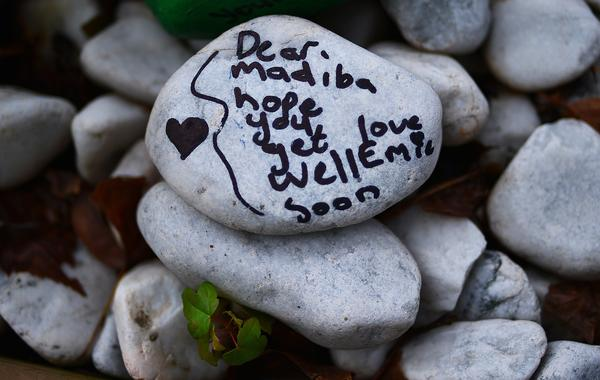 A stone painted with a get-well message and left outside former South African President Nelson Mandela's residence in the Houghton area of Johannesburg on Wednesday. Mandela is known as Madiba.