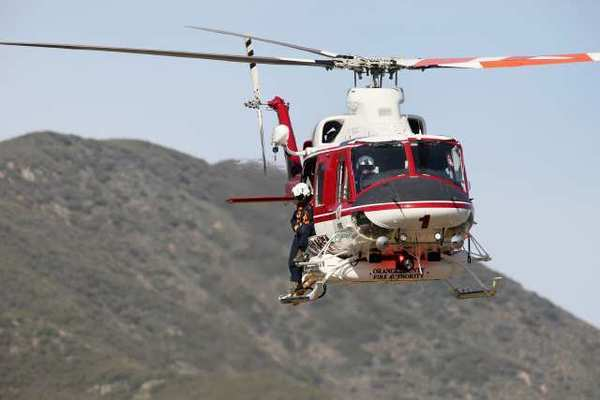 An Orange County Fire Authority helicopter combs the surrounding area where two hikers were reported missing in Trabuco Canyon on Tuesday.