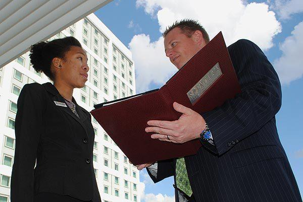 Hilton Orlando Director of Beverage Paul Bishop and UCF hospitality student Daneen Johnson review the beverage menu on Friday, Sept. 23, 2011 on the outdoor terrace of the hotel's steakhouse, Spencer's. Over 70 UCF hospitality students spent the day shadowing industry professionals at more than 20 host organizations as part of the fifth annual Tourism Job Shadow Day, organized by UCF's Rosen College of Hospitality Management and Visit Orlando.
