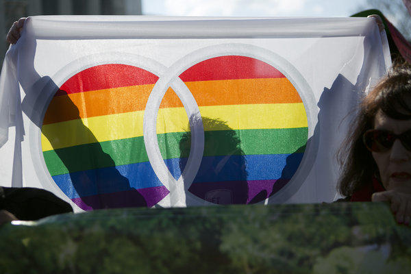 A supporter of same-sex marriage holds a rainbow flag outside the U.S. Supreme Court in Washington, D.C., last week. In Arizona on Tuesday night, the Bisbee City Council approved civil unions regardless of sexual orientation.