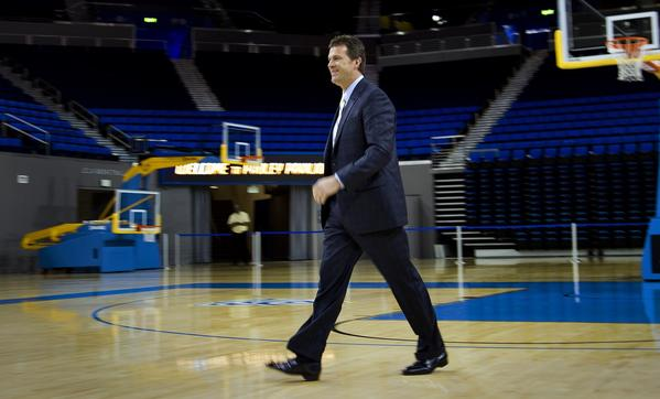 New UCLA Coach Steve Alford heads across Pauley Pavilion to meet with reporters on Tuesday.