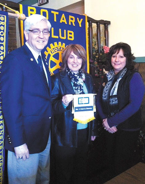 Rotary District Gov. Jim Eberly, left, presents Rotary members Sharon Elbin and Gerri Fischer with awards at a recent meeting of the Rotary Club of Hancock.