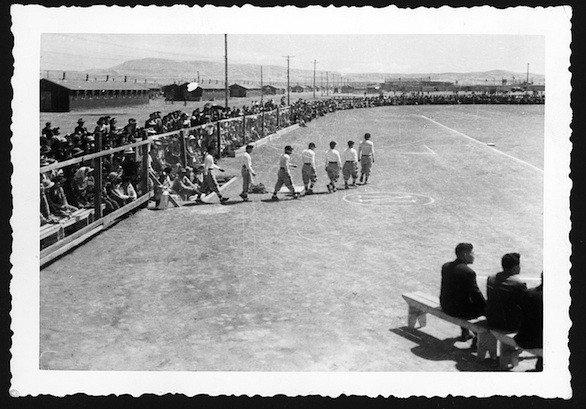 Players walk onto the field before a game at Tule Lake Segregation Center for Japanese Americans in 1944.