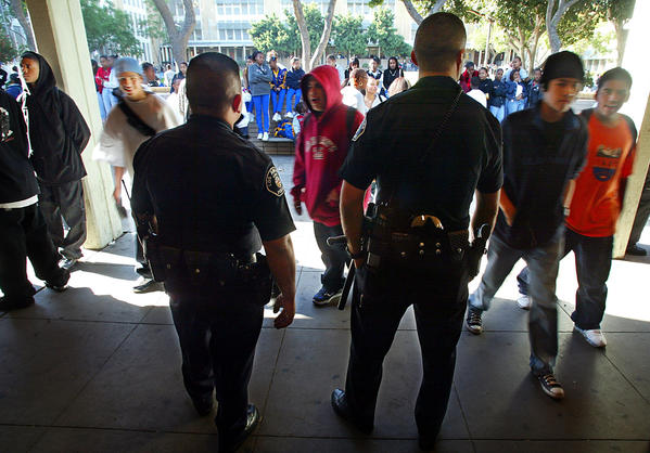 Los Angeles Unified School District Police Officers Alfred Navarro, left, and Luis Barraza keep an eye on students during lunch break at Crenshaw High School in Los Angeles.
