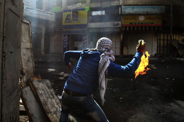 A Palestinian protester throws a Molotov cocktail toward Israeli soldiers during clashes April 3 in the West Bank city of Hebron.