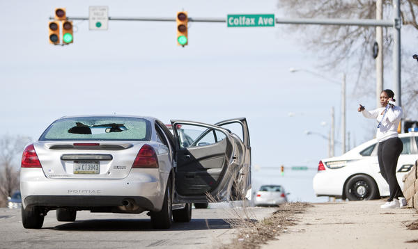 April Redd talks on her phone following a shooting in traffic involving a car carrying Redd's sister-in-law and three children at the corner of Eddy Street and Colfax Avenue in South Bend on Wednesday.